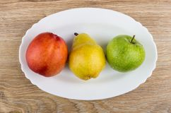 Nectarine, pear and apple in white dish on wooden table. Top view Royalty Free Stock Photos