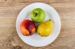 Nectarine, pear and apple in white plate on wooden table. Top view Royalty Free Stock Image