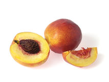 Nectarine and pieces. Tasty juicy pieces of nectarine on a white background with water droplets Stock Photography