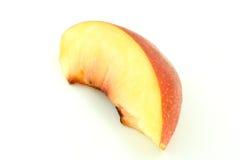 Nectarine slice. Closeup of a freshly cut nectarine slice isolated on white studio background Royalty Free Stock Images