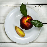 Nectarine in white plate a wooden background. Nectarine with leaf in white plate a wooden background stock image