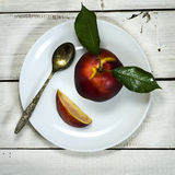 Nectarine in white plate a wooden background. Nectarine with leaf and spoon in white plate a wooden background stock photography