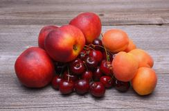 Nectarines, cherries and apricots on wooden table Royalty Free Stock Photography