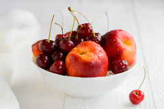 Nectarines, cherries with water droplets in white bowl Stock Image