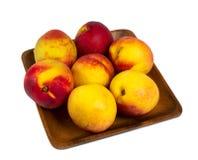 Nectarines dans le plat en bois Photographie stock