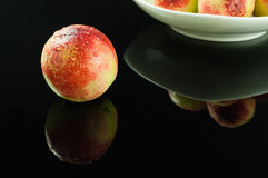 Nectarine with water drop. Fresh nectarine with water drop on black background Royalty Free Stock Photo