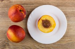 Nectarines and half of nectarine in plate on wooden table Stock Images