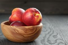 Nectarines in olive wood bowl on oak table Royalty Free Stock Photography