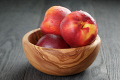 Nectarines in olive wood bowl on oak table Stock Photo