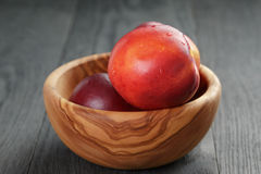 Nectarines in olive wood bowl on oak table Stock Images