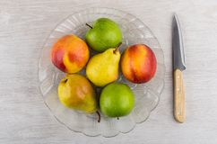 Nectarines, pears, apples in transparent dish and kitchen knife. On wooden table. Top view royalty free stock photos
