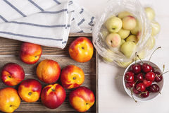 Nectarines, plums and cherries. Studio Still Life with nectarines in the box and plastic bag, sweet cherry in a white cup royalty free stock photography