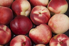 Nectarines. Ripe nectarine fruit at a fruit and vegetable stall in an open air market. Nectarines are used for baking and desserts or usually eaten on their own Stock Image