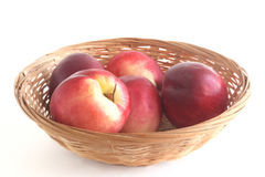 Nectarines in a wicker basket  white background. Five ripe nectarine in a wicker basket  white background Royalty Free Stock Image