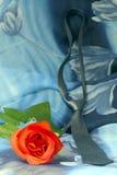 Nectie negro con las rosas rojas en un fondo azul Imagenes de archivo