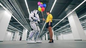 Nedåtgående sikt av en cyborg som accepterar ballonger från en dam stock video