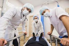 Nedanför sikt av kirurger som rymmer medicinska instrument i händer och ser patienten Royaltyfri Foto
