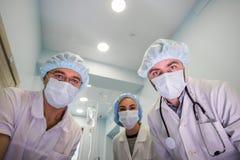Nedanför sikt av kirurger som rymmer medicinska instrument i händer och ser patienten Royaltyfri Bild