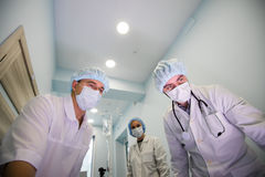 Nedanför sikt av kirurger som rymmer medicinska instrument i händer och ser patienten Royaltyfria Bilder