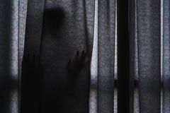 Nederlag för skugga för kvinna` s stående bak gardinen royaltyfri bild