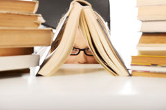 Nederlag för ung kvinna bak en bok arkivfoto