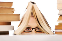 Nederlag för ung kvinna bak en bok royaltyfria foton