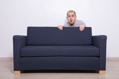 Nederlag för ung man bak en soffa Arkivbild