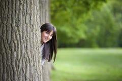 Nederlag för ung kvinna bak ett träd Royaltyfri Bild