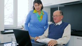 Nederlag i pensionärfamiljeföretag, gift par med datoren som förargas på grund av hopplöshet stock video