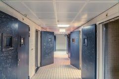 24 Nederland-FEBRUARI: Een lege gang van een gevangenis met tegels op de vloer en de open deuren van de staalcel waarop de tekste stock afbeeldingen