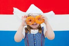 Nederlands meisje met sinaasappel donuts en de vlag van Nederland Royalty-vrije Stock Afbeeldingen