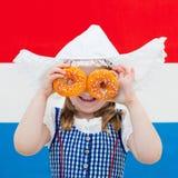 Nederlands meisje met sinaasappel donuts en de vlag van Nederland Stock Fotografie