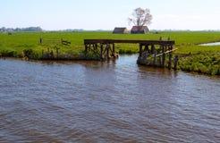 Nederlands platteland met waterweg en gateway Stock Foto