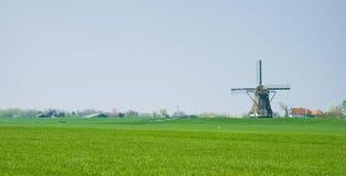 Nederlands polderlandschap met molen en landbouwbedrijven stock afbeeldingen