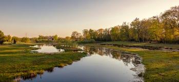 Nederlands rivierlandschap tijdens zonsondergang dichtbij de stad van Almelo stock foto's