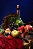 Nederlands stilleven op een fluweeltafelkleed van sappige vruchten en een stoffige oude verticale fles wijn, Stock Foto's
