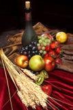 Nederlands stilleven op een fluweeltafelkleed van sappige vruchten, stoffige oude fles wijn en verticale oren van tarwe, Royalty-vrije Stock Foto