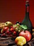 Nederlands stilleven op een tafelkleed van sappige vruchten en een stoffige oude verticale fles wijn op een rode achtergrond, Royalty-vrije Stock Foto's