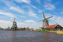 Nederlands typisch landschap Traditionele oude Nederlandse windmolen met huis en blauwe hemel dichtbij rivier in het dorp van Zaa stock afbeelding