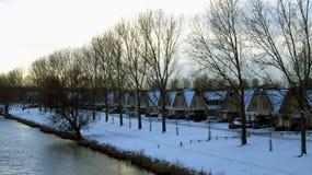 Nederlandse die Huizen langs Kanaal in Sneeuw tijdens de Winter wordt behandeld stock fotografie