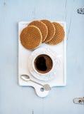 Nederlandse karamel stroopwafels en kop van zwarte koffie op witte ceramische dienende raad over lichtblauwe houten achtergrond Royalty-vrije Stock Afbeeldingen