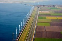 Nederlandse landbouwgrond met windmolens langs de dijk Royalty-vrije Stock Afbeeldingen