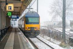 Nederlandse Nationale Spoorwegtrein die het station van Amsterdam verlaten Zuid, die travelors naar Schiphol luchthaven vervoeren stock afbeelding