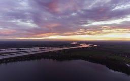 Nederlandse rivier die door het landschap met dramatische zonsondergang winden Royalty-vrije Stock Afbeelding