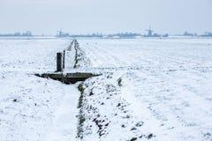 Nederlandse sneeuwlandbouwgrond met windmolens Royalty-vrije Stock Foto
