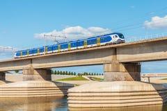 Nederlandse trein die sideskirts van de rivier Waal vooraan o kruisen royalty-vrije stock fotografie