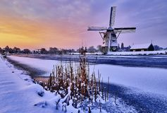 Nederlandse windmolen in de sneeuw van de winter van Holland stock foto