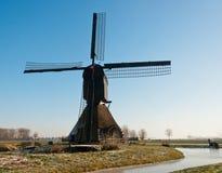 Nederlandse windmolen en een bevroren sloot Stock Foto