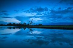 Nederlandse windmolen en wolken in schemer Stock Foto