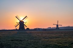 Nederlandse windmolens bij zonsondergang dichtbij Leiderdorp, Holland stock foto's